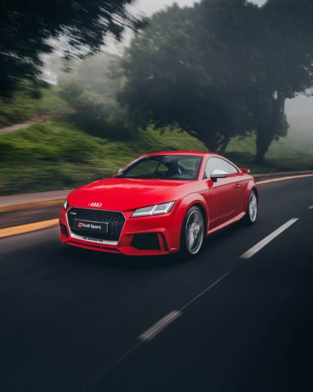 red Audi coupe on road near trees at daytime