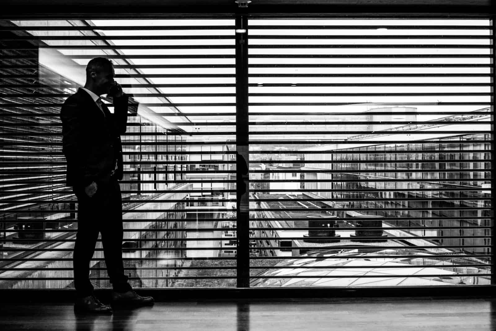 silhouette of man standing beside clear glass wall while using smartphone